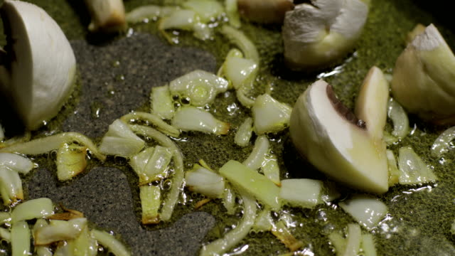 Close up of delicious sliced button mushrooms being fried with onion on the pan video
