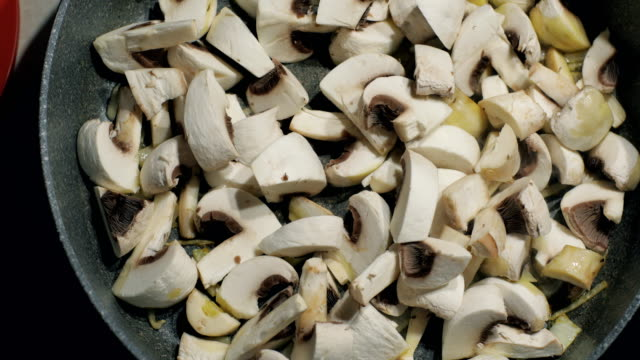 Close up of delicious sliced button mushrooms being stir-fried fried with onion on the pan video