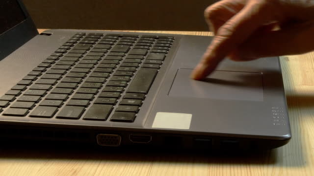 Close up of elderly man hands using laptop at home video