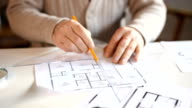 Close up of elderly man's hands drawing on blueprints video