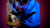 Close up of face of a young girl standing with the pink flower in her hands and her face with art paiting in Halloween theme. Phantom of young girl is standing in the dark room in white wedding dress video