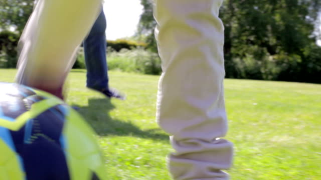 Close Up Of Feet As Grandfather And Grandson Play Football video