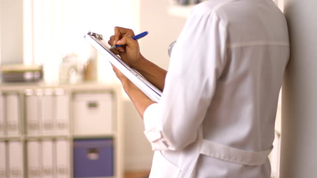 Close up of Female Doctor's hands writing on chart video