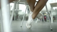 Close up of female legs with sport shoes under wooden table. video