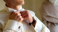 Close up of groom corrects the necktie video