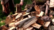close up of hand chop with axe thick wood near woodpile video