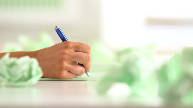 Close up of hand writing with crumpled paper on desk video