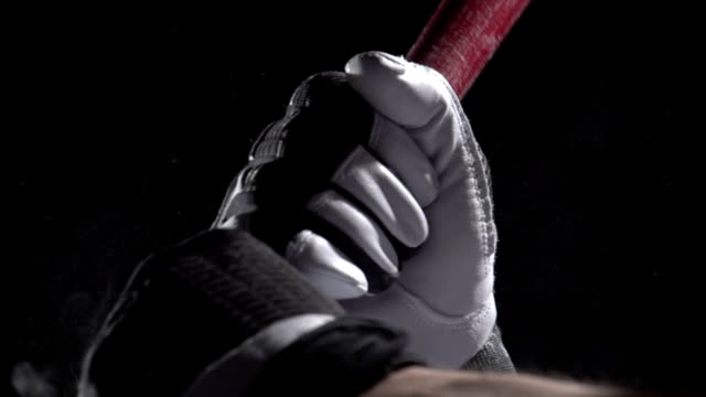 Close up of hands on a baseball bat, slow motion video