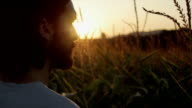 Close up of handsome man with beard with nature landscape in sunset/sunrise. video