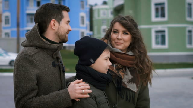 Close up of happy young family in warm clothing standing together on the street smiling. Father and mother are laughing and looking happily to each other and their son video