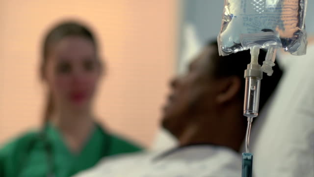 Close up of IV with nurse and patient video