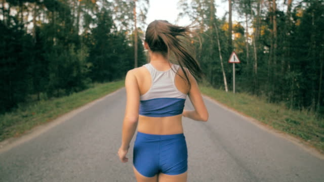 Close up of jogging shoe and legs of jogger. Back side view of a female athlete training outside on road in park video
