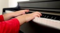 Close up of little girl hands playing piano video