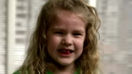 Close Up of little girl with blonde curly hair, smiling video