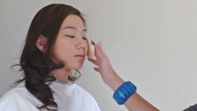 Close up of make-up artist applying foundation with a brush on young woman's face. video