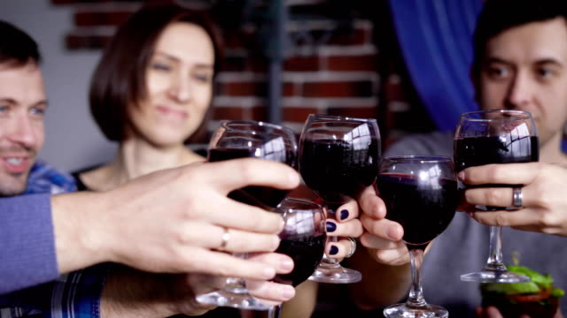 Close up of male and female hands clinking glasses with red wine to each other with happy faces in the background. Group of people celebrating party at the restaurant talking and smiling video