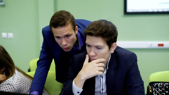 Close up of male college students dressed in suits working together in classroom and using laptop for doing practical work. Two young students are looking at monitor video