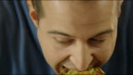 Close up of man biting a burger 4K video