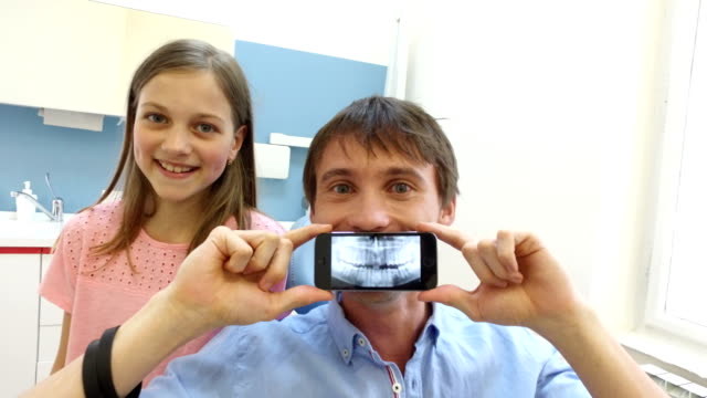 Close up of man holding smartphone with photo of dental X-ray at dentist video