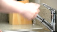 Close up of man washing hands in kitchen sink video