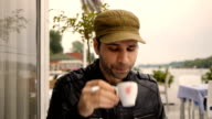 Close up of mans with a hat drinking hot coffe, smoking cigarrete, enjoying outdoors in caffee video