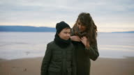 Close up of mother and son in warm clothes standing on the shore together with the sea behind. Mother is saying something to her son setting her scarf, then she is embracing him video