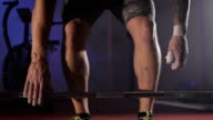 Close up of muscular athlete in shirts going to the barbell and lifting it in slow motion video