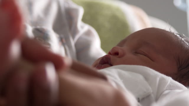 Close Up Of Parents Cuddling Newborn Baby Son In Nursery video