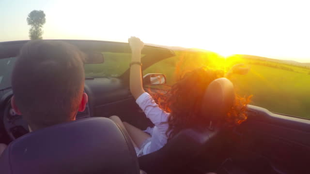 Close up of party couple with hands up, driving convertible, cabriolet car, at sunset with sun flare. Steadicam shot.. UHD 4K stock footage video
