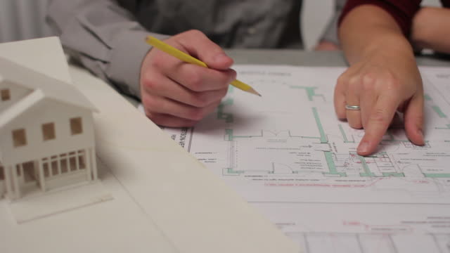 Close up of people going over architecture plans video