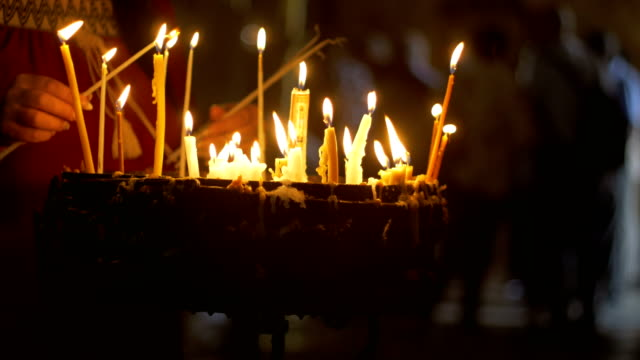 Close up of prayers hands lighting candles in the  Church of The Holy Sepulchre in Jerusalem video