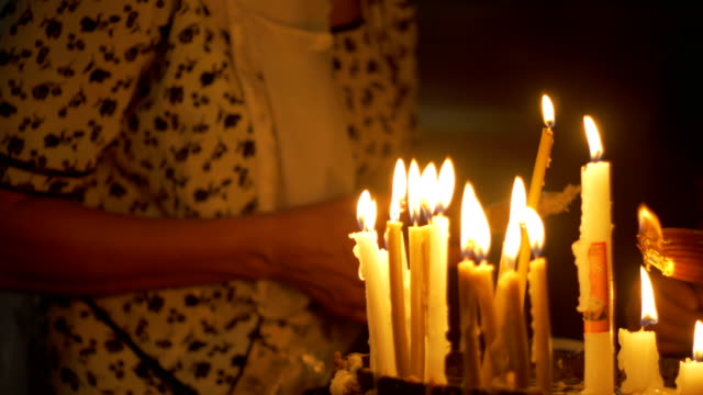 Close up of prayers hands lighting candles in the Holy Sepulchre Church in Jerusalem video