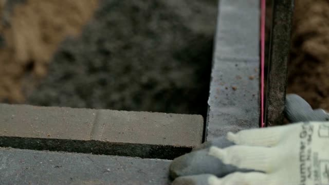 Close up of professional putting tile in place in drainage video