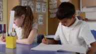 Close Up Of Pupils Working At Desks In Classroom Shot On R3D video