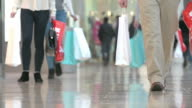 Close Up Of Shopper's Feet Carrying Bags In Shopping Mall video