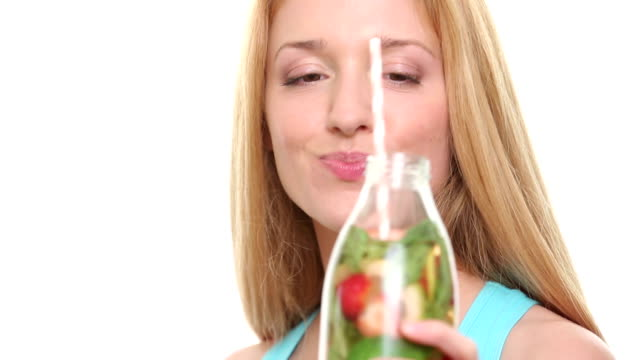 Close up of slim woman with fruit detox water in glass bottle on white background. video