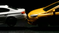 ACCIDENT: Close up of toy model car crashes to white toy car (slow motion) video
