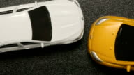 TOP VIEW: CAR ACCIDENT - Close up of toy model car crashes to white toy car (slow motion) video