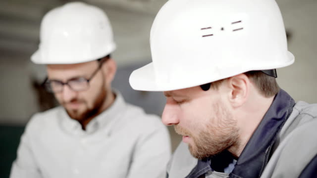 Close up of two bearded men in protective helmets working together in construction area. Foreman and worker are standing on building site. Builders are discussing current project laughing and smiling video