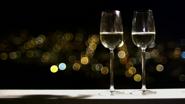 Close up of two champagne flutes with the city lights of San Francisco at night behind them video