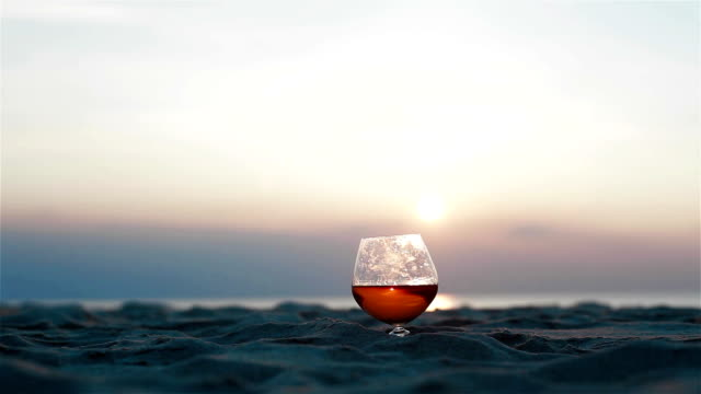Close up of two glasses of brandy standing on the sand over incredible beach sunset background view. Male hand gallantly takes glasses away and then places back to the sand surface video