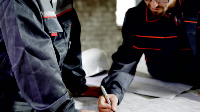 Close up of two professional engineers making construction project drawings. Two men working with sheme of future building. Architect and foreman drawing on design documentation of current project video