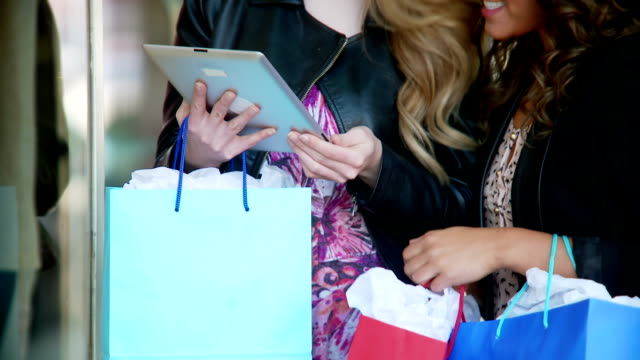 Close up of two women shopping with tablet video