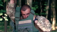 Close up of warrior wears body armor in the forest. Slow motion video