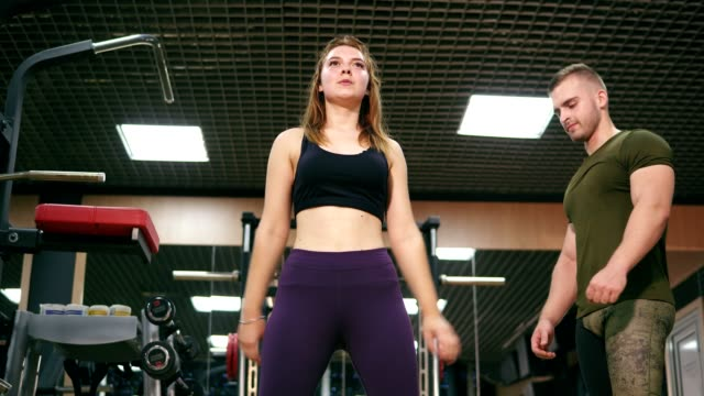 Close up of woman doing back squat backed up by her personal instructor in the gym. Young girl exercising doing squats while her trainer is watching her technique. Shot in 4k video