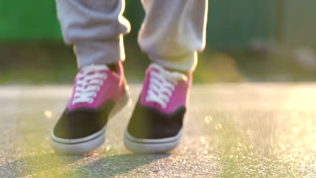 Close up of woman feet jumping, using skipping rope in park. Slow motion video