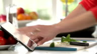 Close Up Of Woman Following Recipe On Digital Tablet video