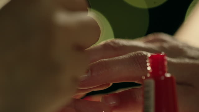 Close up of woman getting red nail polish applied on her nail by make up artist. video