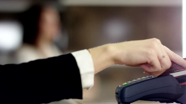 close up of woman paying for room in the hotel at the reception and get a key video