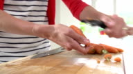 Close Up Of Woman Peeling Carrots On Wooden Board video